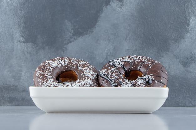 Weiße schüssel mit zwei schokoladenkrapfen auf steinhintergrund. foto in hoher qualität