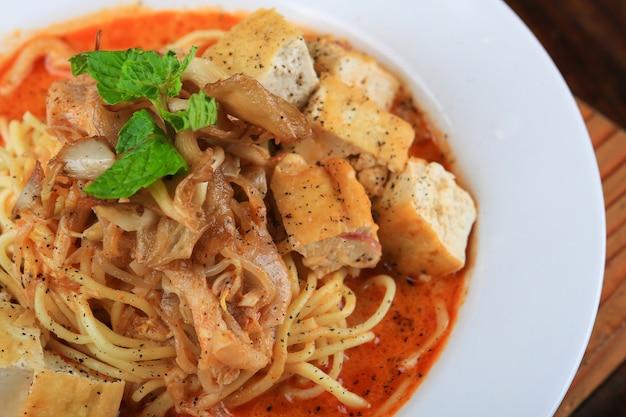 Weiße schüssel suppe mit einigen spaghetti und brotstücken, die mit gemüse verziert sind