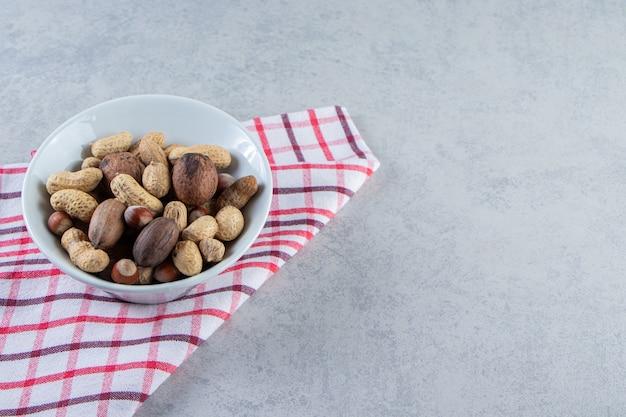 Weiße schüssel voller verschiedener geschälter nüsse auf steinhintergrund.