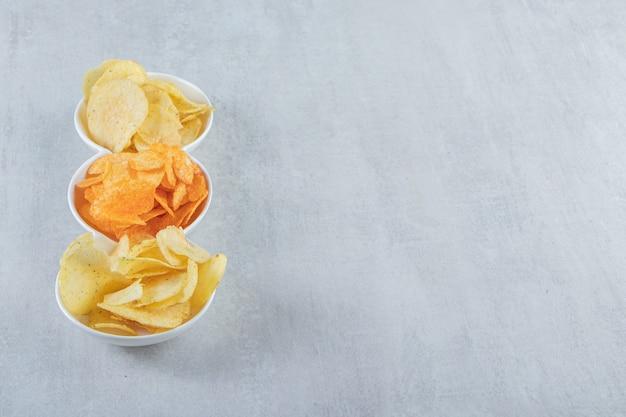 Weiße schüsseln mit köstlichen verschiedenen chips auf stein.