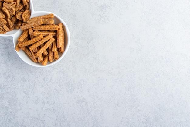 Weiße schüsseln mit leckeren knusprigen crackern auf steinhintergrund.