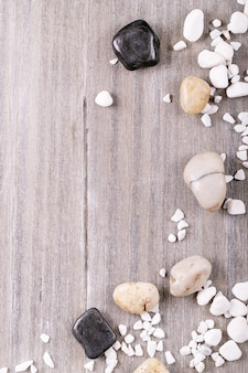 Weiße, schwarze dekorative felsen und kieselsteine über grauem hölzernem hintergrund. draufsicht, flach liegen. speicherplatz kopieren