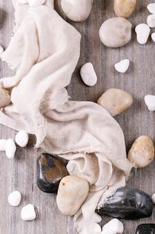 Weiße, schwarze dekorative steine und kieselsteine über grauer holzoberfläche. draufsicht, flach liegen. speicherplatz kopieren