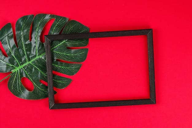 Weiße schwarze rahmengrenze des tropischen blattes des sommerideenkonzeptes auf rot