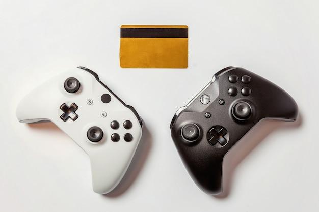 Weiße schwarze zwei-joystick-gamepad-spielekonsole goldene kreditkarte lokalisiert auf weißer wand. computerspieltechnologie spielen wettbewerb videospielsteuerung konfrontationskonzept cyberspace-symbol