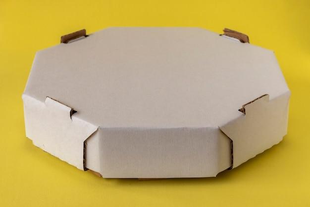 Weiße sechseckige schachtel für die lieferung von lebensmitteln. gelber hintergrund.