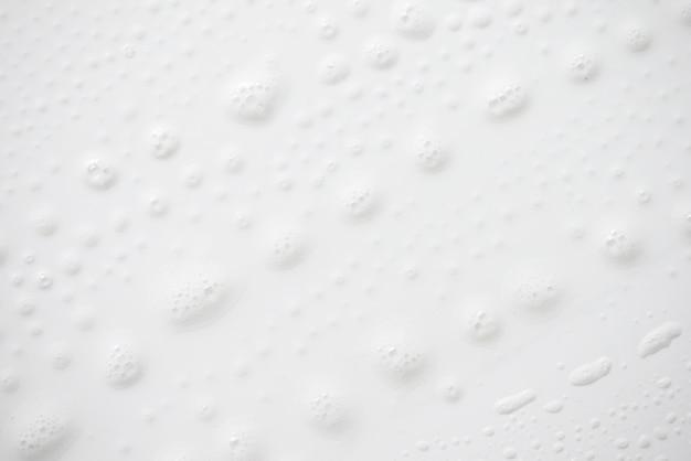 Weiße seifige schaumbeschaffenheit des abstrakten hintergrundes. shampooschaum mit blasen