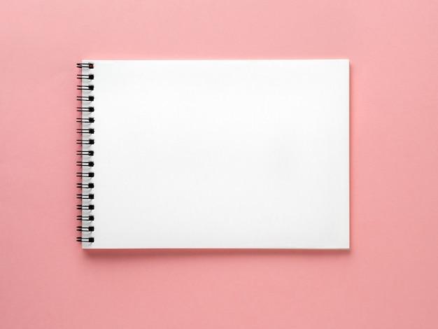 Weiße seite des leeren notizblockes auf rosa schreibtisch, farbhintergrund. draufsicht, flach zu legen.