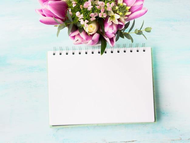 Weiße seite des leeren notizbuches mit purpurroten rosa blumen. hintergrund copyspace