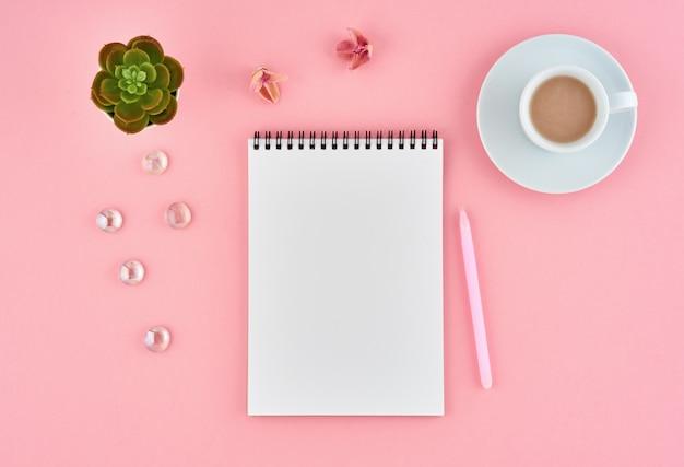 Weiße seite und schale des leeren notizblockes kakao auf rosa schreibtisch