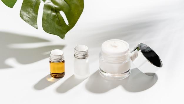 Weiße serumflasche und cremetiegel, marke für schönheitsprodukte. draufsicht auf den weißen hintergrund.