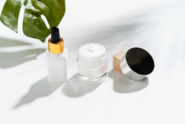 Weiße serumflasche und cremetiegel, modell der schönheitsproduktmarke. draufsicht auf den weißen hintergrund.