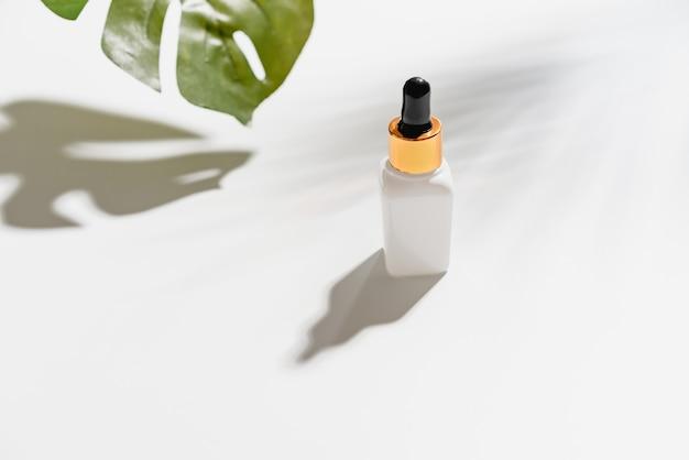 Weiße serumflaschencreme, modell der schönheitsproduktmarke in der flachen lage