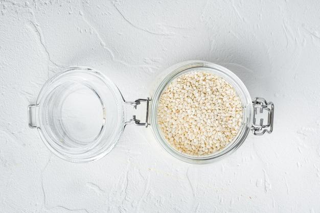 Weiße sesamkörner im glas auf weißem stein