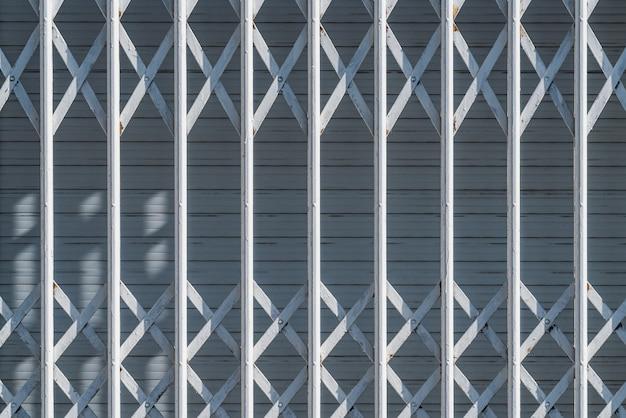 Weiße sicherheitsgitter an einem stadtfenster mit geschlossenem verschluss