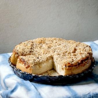 Weiße sizilianische focaccia. traditionelles gebackenes brot in scheiben geschnittener kuchen mit zwiebeln, kräutern und käse in keramikschale, serviert auf blau-weißer tischdecke. quadratisches bild