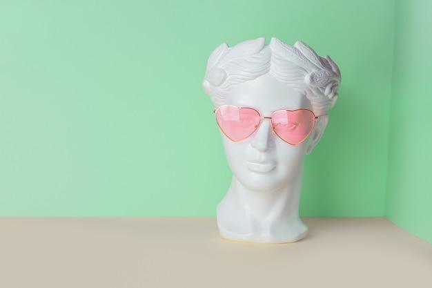 Weiße skulptur eines antiken kopfes in rosa gläsern mit herzen. auf einem geometrischen hintergrund von zwei farben.