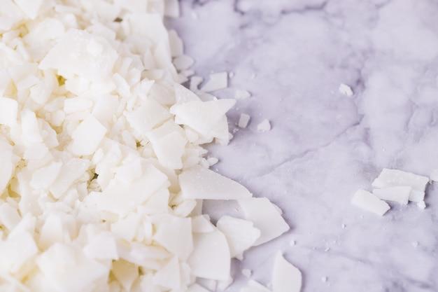 Weiße sojawachsflocken für die kerzenherstellung auf einem hellgrauen marmortisch