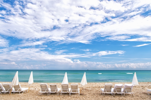 Weiße sommer-liegestühle und geschlossene sonnenschirme, die an der leeren ozeanküste mit sand und bewölktem blauem himmel in south beach, miami, florida, in einer schlange stehen?