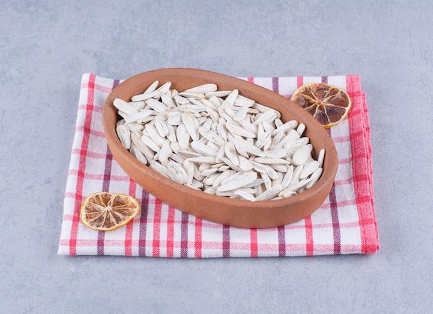 Weiße sonnenblumenkerne in der schüssel neben getrockneter zitrone auf geschirrtuch auf marmor.