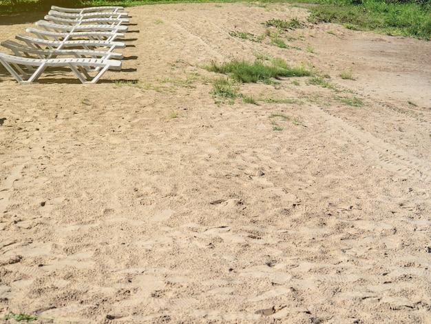 Weiße sonnenliegen am sandigen ufer des stausees sommerurlaub. platz kopieren.