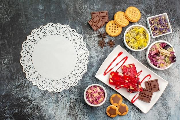 Weiße spitze mit einem schokoladenteller mit trockenen blumen und keksen auf grauem hintergrund
