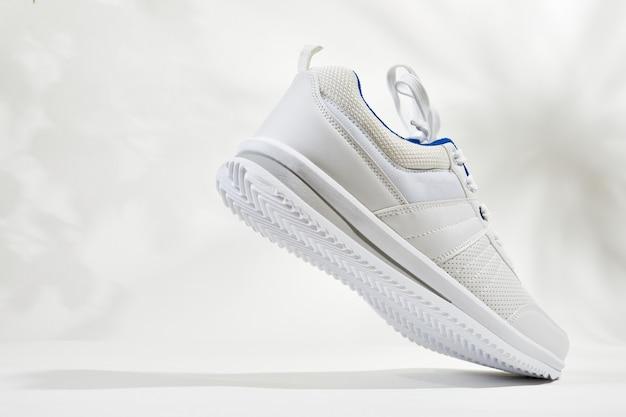 Weiße sportschuhe mit schnürsenkeln an einer weißen wand. mann turnschuhe für fitness. weißer sneaker mit lederakzenten.