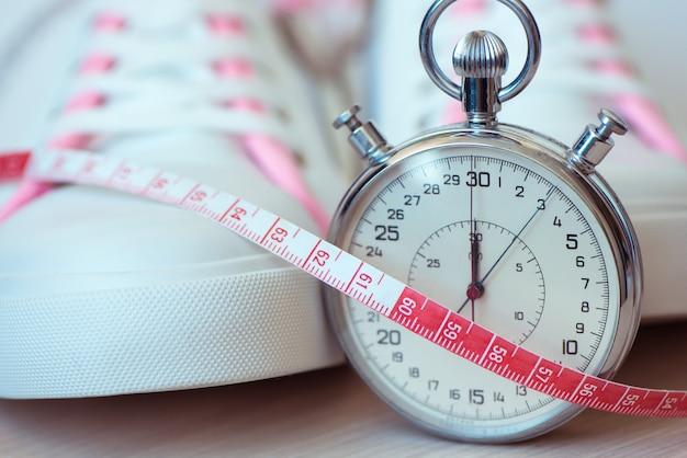 Weiße sportschuhe, timer und maßband. konzept von fitness, sport, gesundem lebensstil.