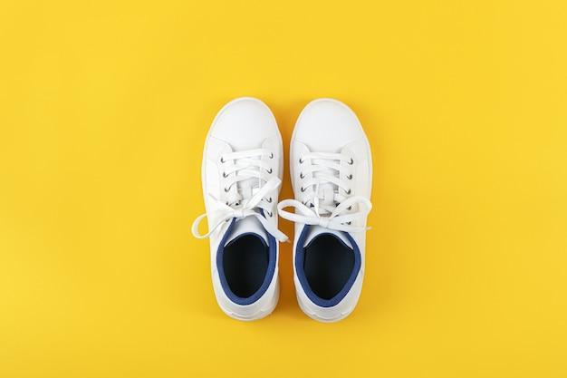 Weiße sportschuhe, turnschuhe mit schnürsenkeln auf gelbem grund. sport-lifestyle-konzept