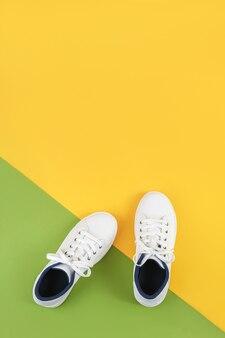 Weiße sportschuhe, turnschuhe mit schnürsenkeln auf grün und gelb