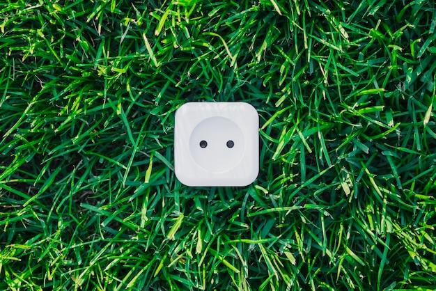 Weiße steckdose auf grünem gras