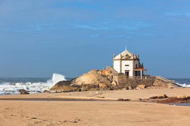 Weiße steinkapelle an einem sandstrand am meer. portugal