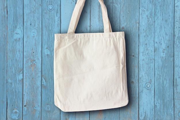 Weiße stofftasche, die an der blauen wandmocap hängt, ein platz für text oder leichte öko-tasche zum zeichnen