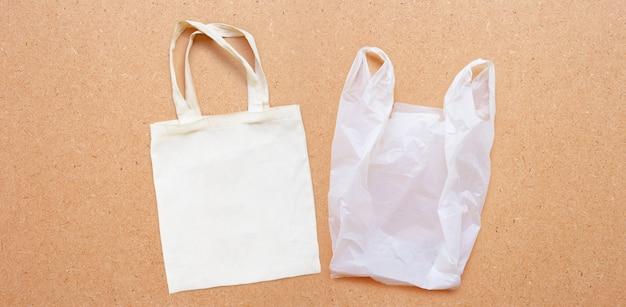 Weiße stofftasche mit weißer plastiktüte auf sperrholz.