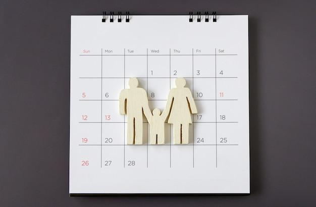 Weiße symbolfamilie auf kalender, familienkonzept