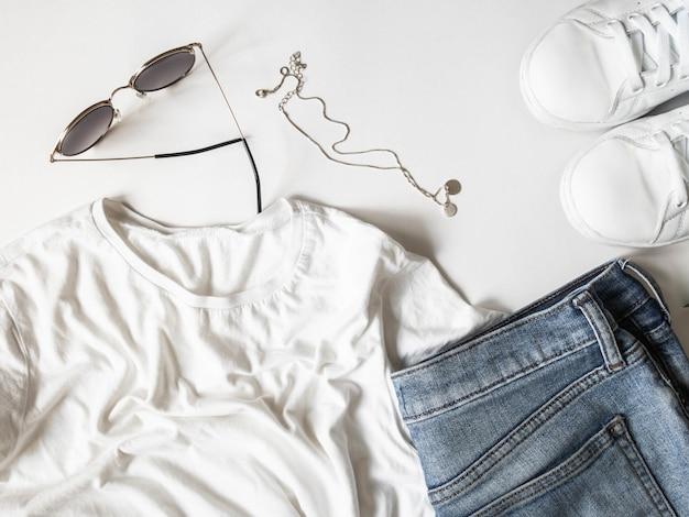 Weiße t-shirt blue jeans, sonnenbrille, halskette und weiße turnschuhe auf weißem hintergrund.