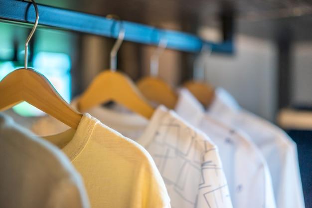 Weiße t-shirts, die an der schiene in einer garderobe, innenarchitektur hängen. innenräume.