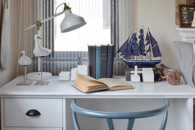 Weiße tabelle mit holzstuhlbüchern und -lampe i
