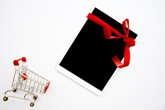Weiße tablette in der nähe von einkaufswagen