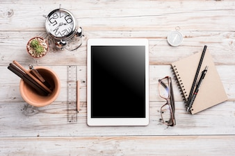 Weiße Tablette mit leerem Bildschirm auf hölzernem Schreibtisch mit Briefpapier wendet, Draufsicht ein