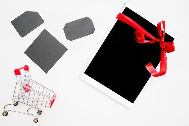 Weiße tablette nahe grauen tags und einkaufslaufkatze