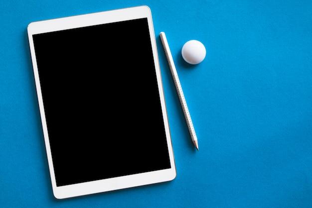 Weiße tablette und bleistift auf blauer oberfläche
