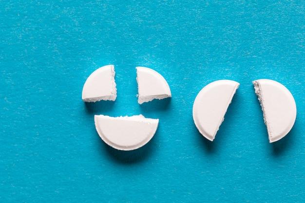Weiße tabletten der pharmazeutischen medizin auf blau. kopieren sie platz für text
