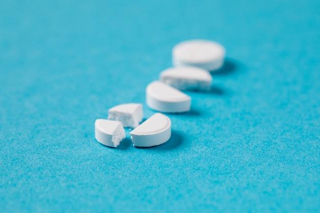 Weiße tabletten der pharmazeutischen medizin auf blauem hintergrund. kopieren sie platz für text