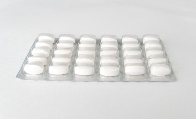 Weiße tabletten tabletten in packung auf einem weißen
