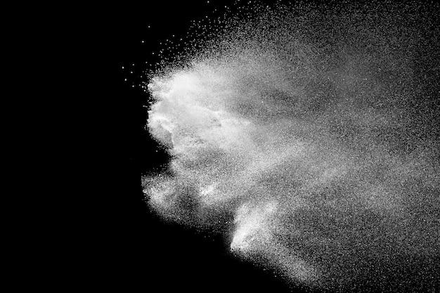 Weiße talkumpulver-explosion auf schwarzem hintergrund