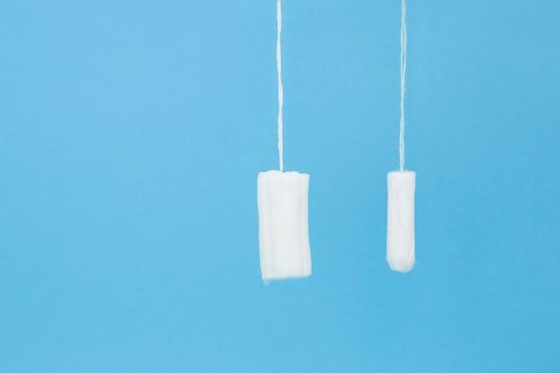 Weiße tampons auf blauem hintergrund. frauenhygiene