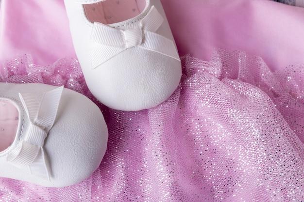 Weiße tanzschuhe des kleinen mädchens nahe trikots