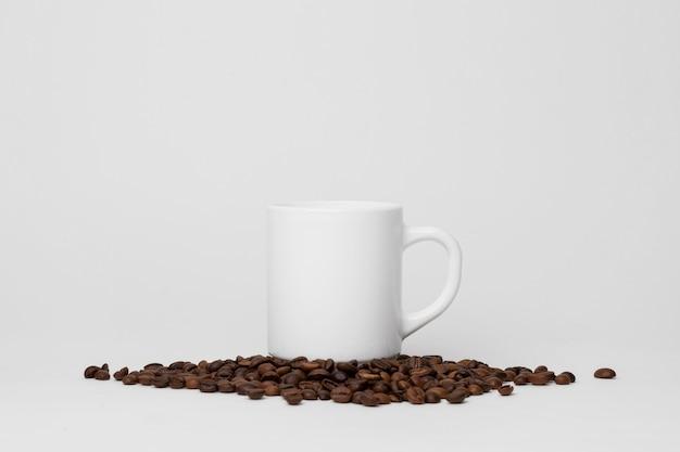 Weiße tasse auf kaffeebohnenanordnung