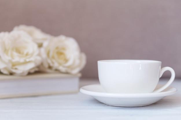 - weiße tasse auf weißem holzhintergrund mit rosen. hochzeit, romantisch.